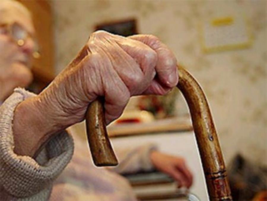 Рука пенсионера с тростью