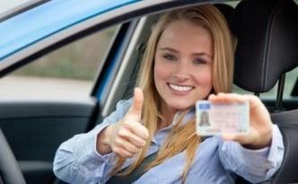 девушка держит водительское удостоверение
