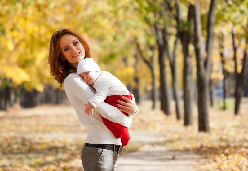 Женщина с ребенком на руках в парке