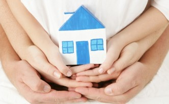 Ребенок держит в руках макет дома