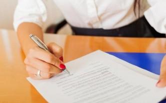 Женщина ставит подпись на документе