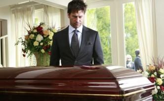 Мужчина стоит перед гробом